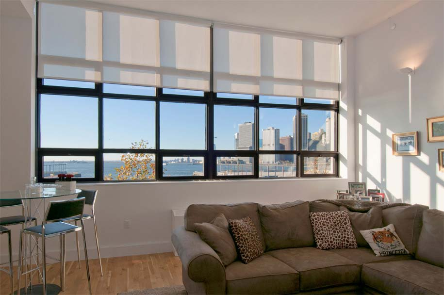 white electric solar shades on high and tall windows, living room at One Brooklyn Bridge Park, 360 Furman installed by Horizon Window Treatments