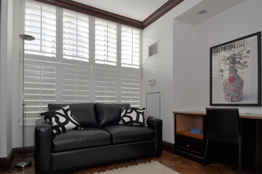 White shutters on a floor to ceiling windows, living room at the Beekman Regent 351 East 51st Street installed by Horizon Window Treatments